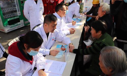 我院医生在公益筛查现场记录患者病情并为患者免费体检