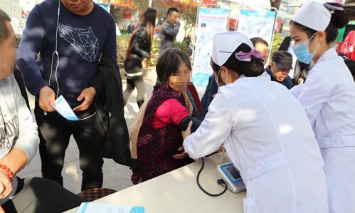 义诊活动中,医护人员为老人进行血压测量